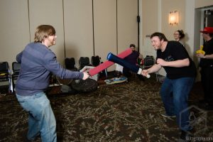 Two Penguicon-goers in a mock battle with foam swords