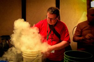 Penguicon-goer with a vapor cloud making liquid nitrogen ice cream in a bucket