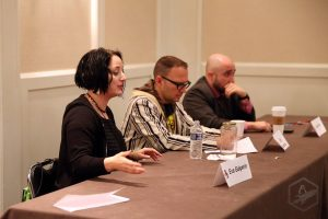 Three panelists, including Eva Galperin, at long table
