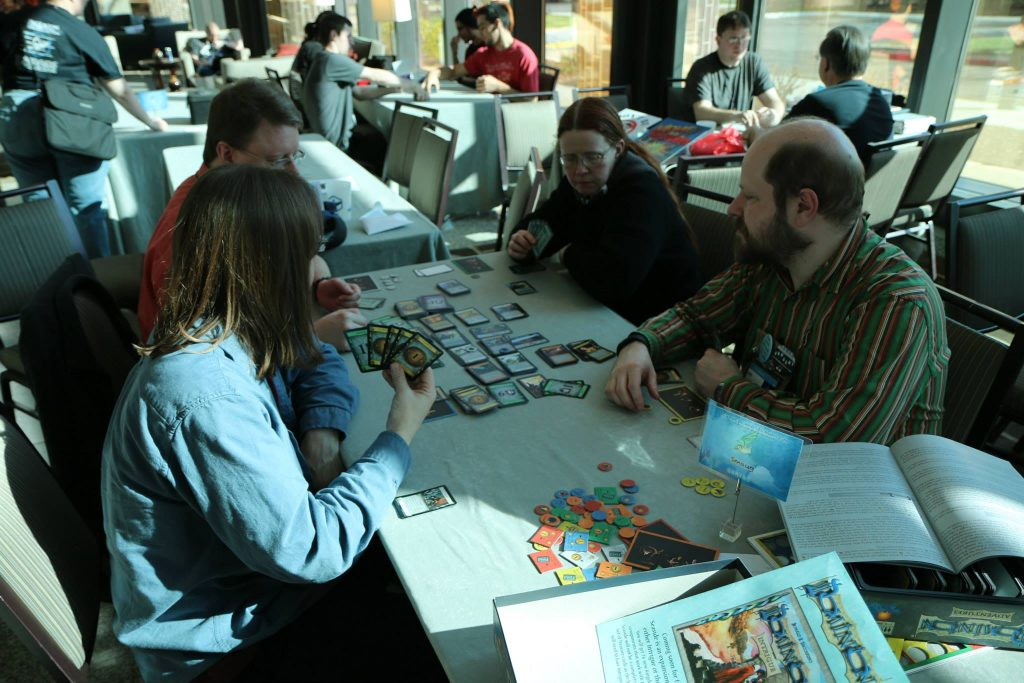 Group playing the deck building game Dominion with other groups in the background playing games